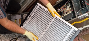 A man putting in a new air filter