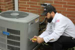 HVAC technician unscrewing side panel of AC unit