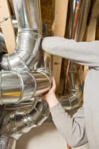 Repair person inspecting ductwork