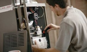 HVAC technician repairing an electric furnace