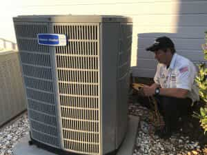 HVAC Technician Tuning Up an AC Unit