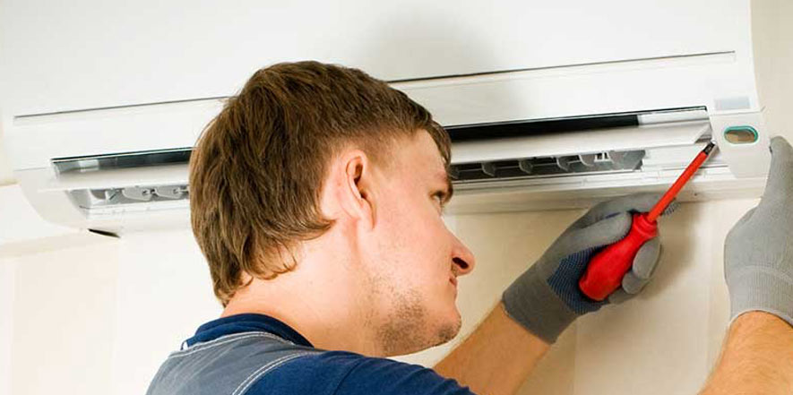 Man working on a ductless mini split AC system